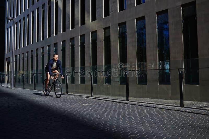 Tour ttractive de jeune homme de  de Ð sur la bicyclette fixe de vitesse regardant loin images libres de droits