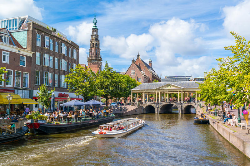 Tourboat on New Rhine canal, Leiden, Netherlands. People in tourboat on canal cruise, town hall tower, outdoor terrace of cafe and Korenbeursbrug bridge over New royalty free stock image