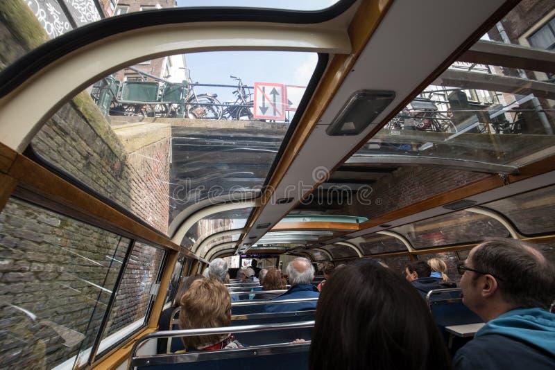 Tourboat tar turister runt om kanalerna i Amsterdam Fartyget går under en bro Klassisk arkitektur- och fartygflank arkivfoto
