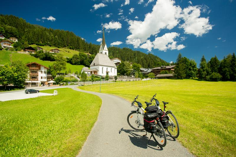 Touring bicycles in a village in Austria. Touring bicycles and church in a village in Austria royalty free stock photography