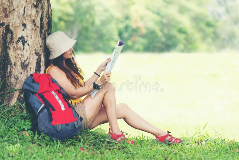 Tourism asian lifestyle women and traveler with backpack adventure holding map to find directions in the jungle forest destination royalty free stock photo