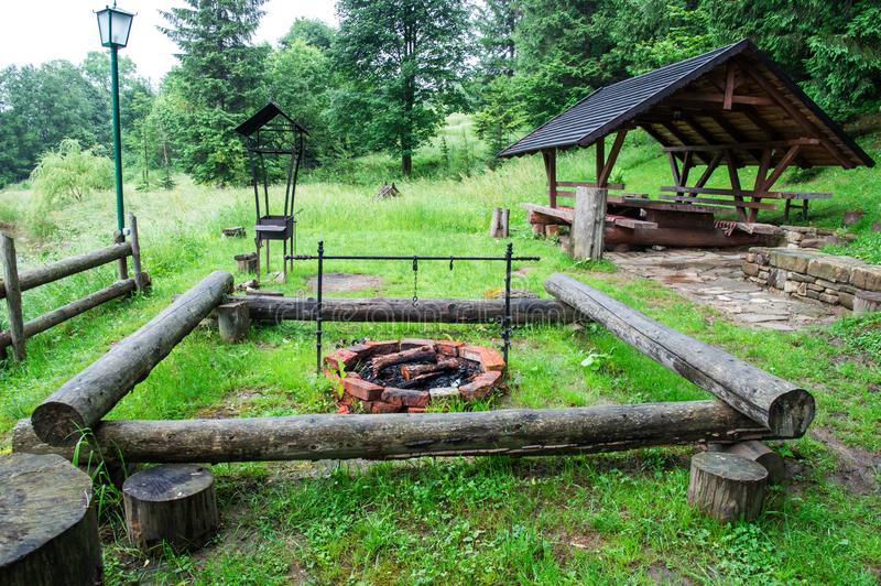 Tourism in the Carpathians. BBQ area. Stone fireplace for cooking outdoor. Inside the firewood and burnt coals. Green coniferous royalty free stock photos
