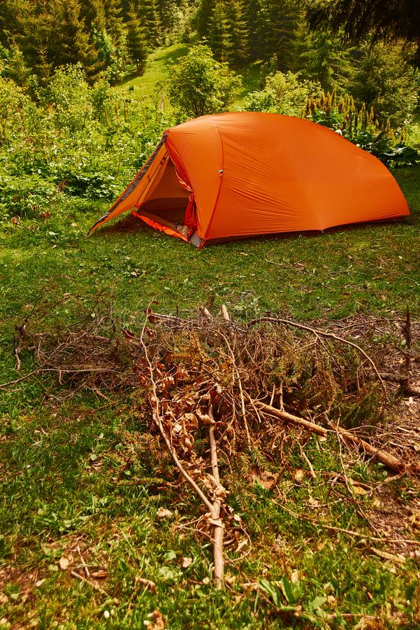 Tourism day, camping. bright orange tent set up by tourists in the forest in the mountains royalty free stock photos