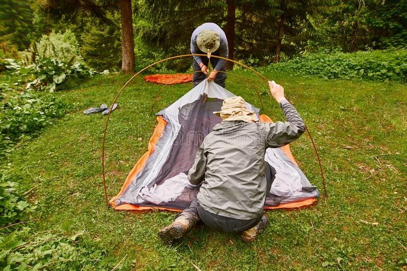 Tourism day. tourists - two men in tourist clothes and with special equipment - put up a tent in a camping stock image