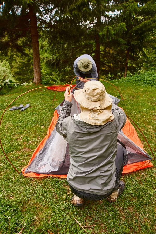 Tourism day. Camp in the tent - tourists setting a tent on the camping. Close up man`s hands hold a tent while setting up a tent royalty free stock photography
