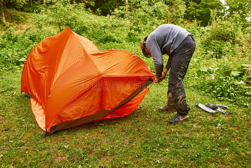 Tourism day. tourists - two men in tourist clothes and with special equipment - put up a tent in a camping stock photos