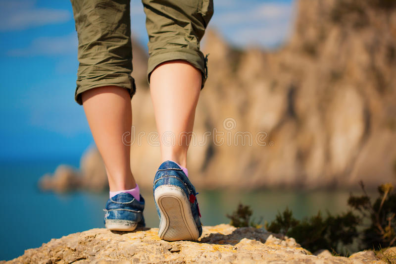 Tourism. female feet in sneakers stock photography
