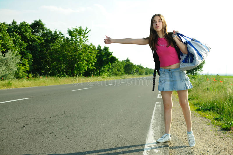 Tourism hitchhiking. Young girl hitchhiking on the road royalty free stock images