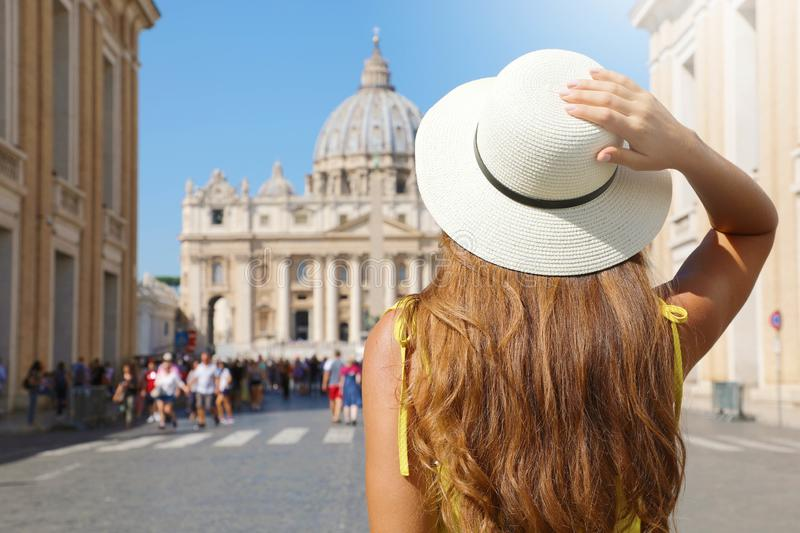 Tourism in Italy. Back view of young tourist woman walks along Via della Conciliazione street in Rome with St Peter Basilica and. Crowd of tourists on the stock photography
