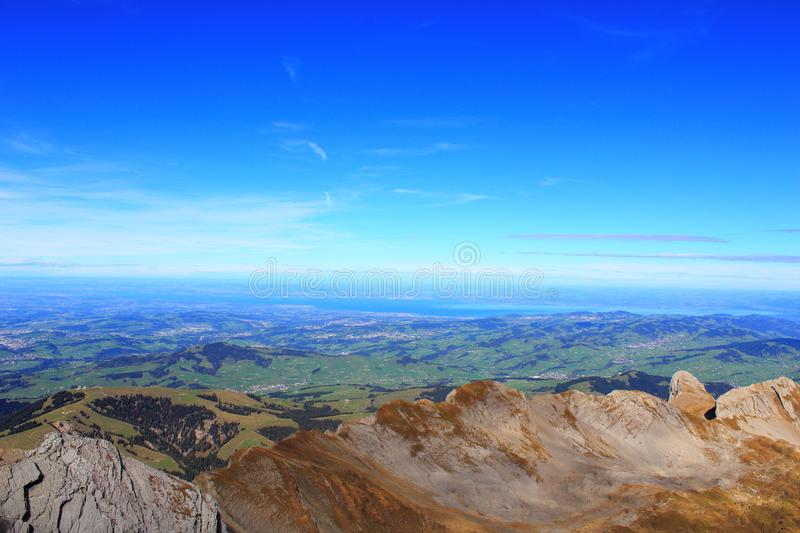Tourism. Leisure. Mountain panorama. View of the adjacent mountain valley with nearby villages on a clear sunny day. Holidays in the mountains. Gorgeous mountain royalty free stock photography
