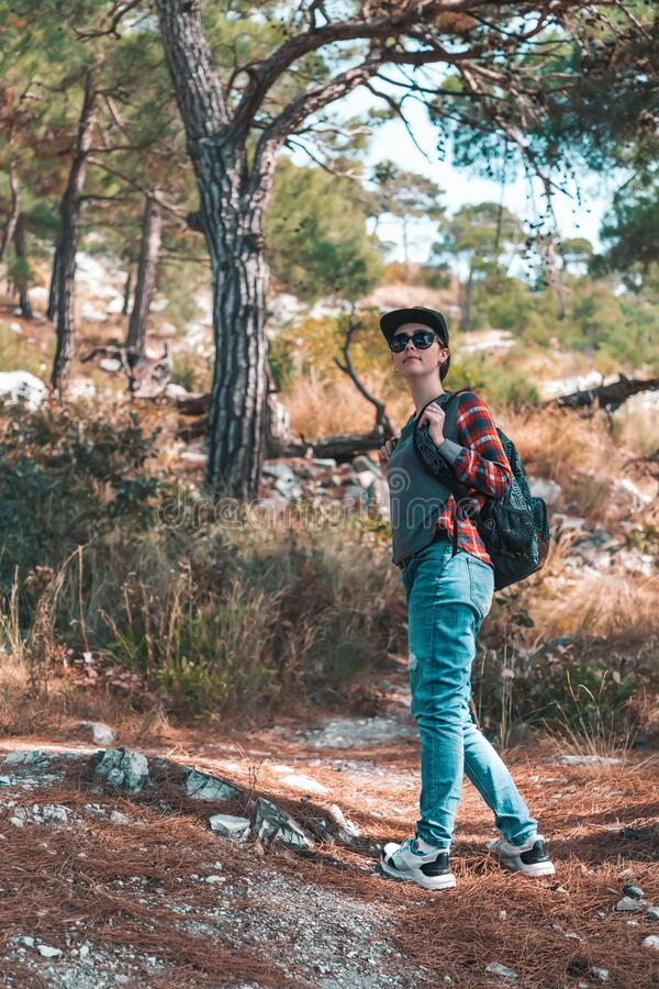 Tourism and outdoor activities. A woman with a backpack on her back is engaged in walking in the woods. Vertical orientation.  royalty free stock image