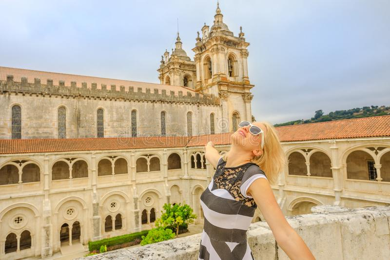 Alcobaca Monastery woman tourist. Tourism in Portugal. Carefree blonde lifestyle tourist at Alcobaca medieval monastery and Church with gothic tower. An Elegant royalty free stock images