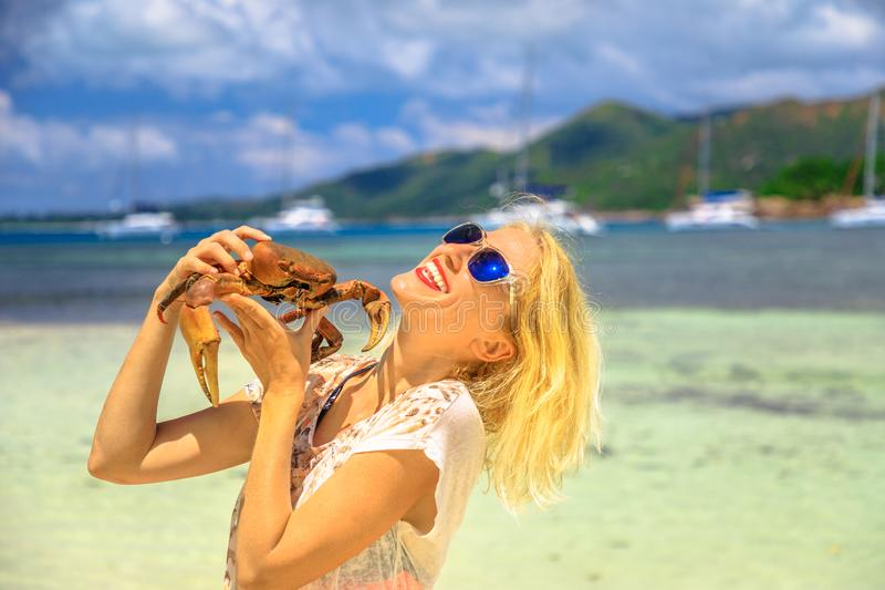Woman with Ghost Crab. Tourism in Seychelles, Africa, Indian Ocean. Happy tourist woman holding an Ocypode Ceratophthalmus also called Ghost Crab with one claw stock photos