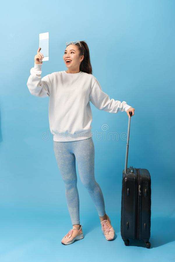 Tourism, summer holidays and vacation concept - Happy woman in casual clothing with travel bag and air ticket over blue background stock photography