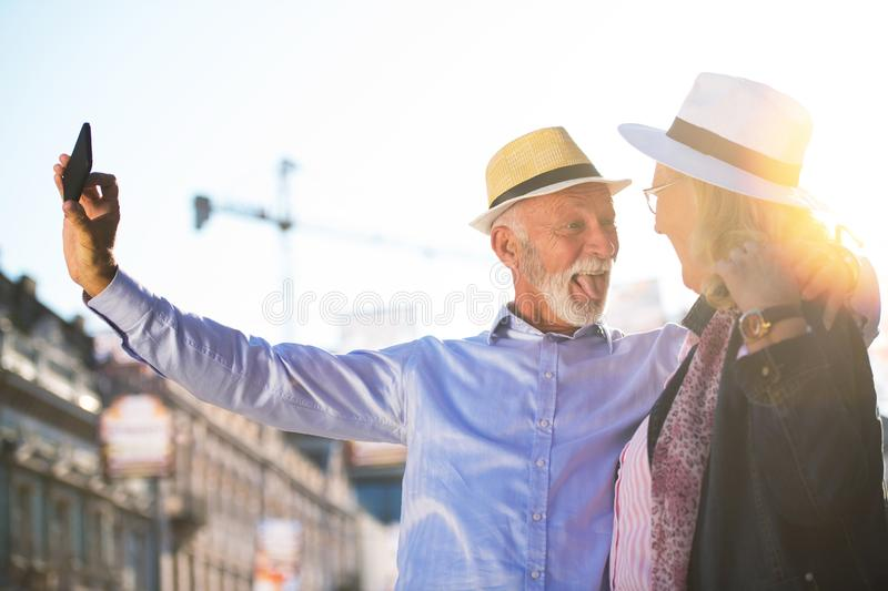 Tourism and technology. Traveling senior couple taking selfie together against sightseeing background. royalty free stock photo