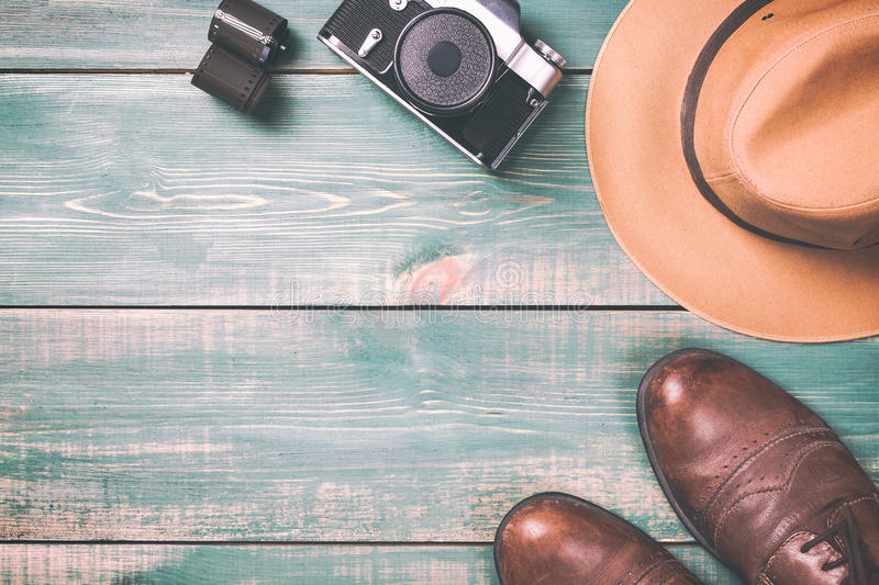 Tourism and travel concept. Vintage camera with film, brown shoes and fedora hat on green wooden background. Toned image and free stock photos