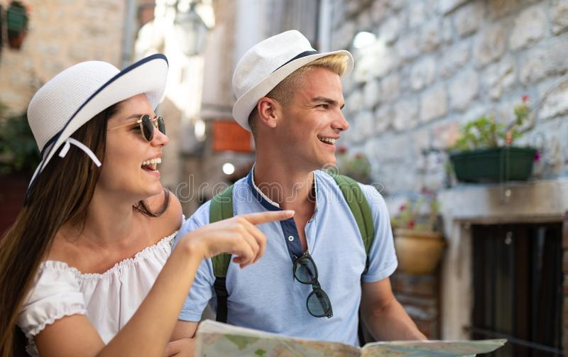 Smiling gorup of friends with map. Tourism, travel, leisure, holidays and friendship concept royalty free stock photos