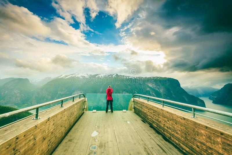 Tourist photographer with camera on Stegastein lookout, Norway. Tourism and travel. Woman tourist nature photographer taking photo with camera, enjoying Aurland stock photography