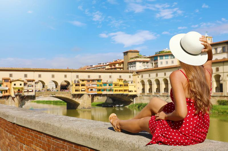 Tourism in Tuscany. Rear view of young fashion woman sitting and looking at Ponte Vecchio bridge in Florence, Italy stock photo