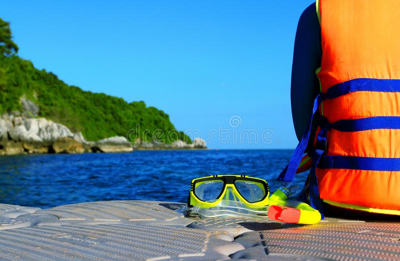 Tourism wearing orange life jacket or life vest and sitting on the float with yellow snorkel mask. Safety, Sport Activity and Vacation time concept royalty free stock photo