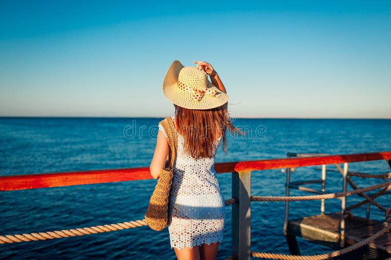 Tourism. Young woman traveler admiring landscape on pier by Red sea. Summer fashion royalty free stock photos