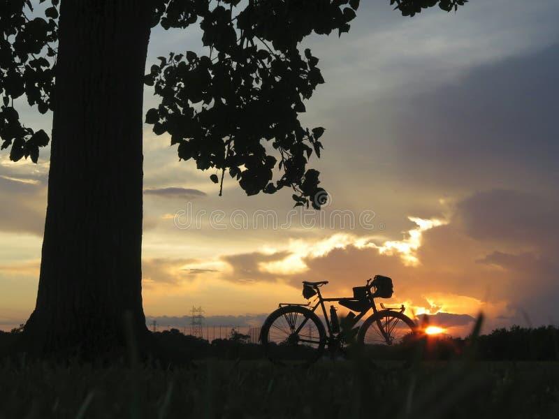 Tourisme de la silhouette de vélo au coucher du soleil photo stock