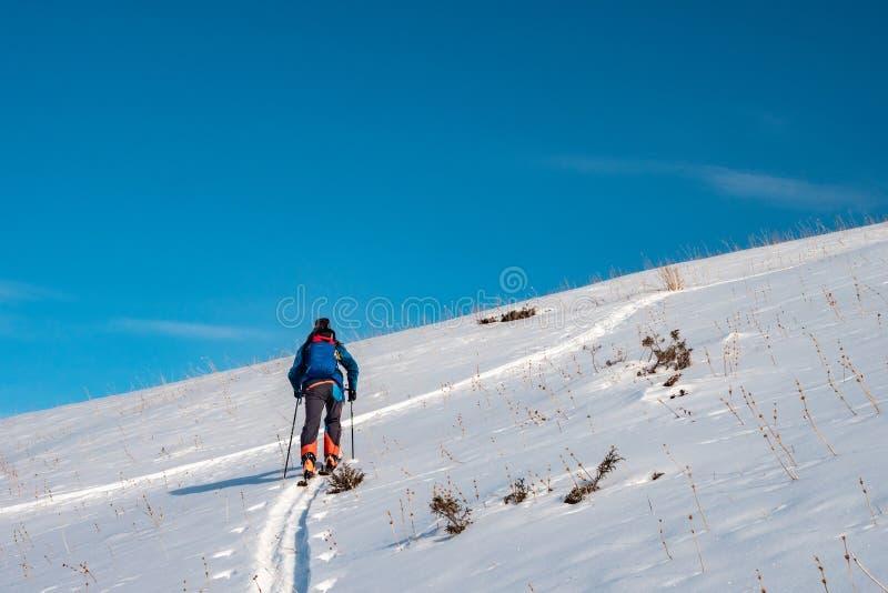 Tourisme de ski Un homme escalade la colline Sport d'hiver photographie stock