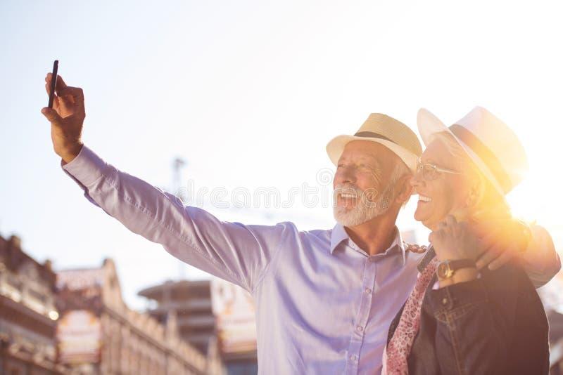 Tourisme et technologie Couples supérieurs de déplacement prenant le selfie ensemble sur le fond guidé image stock