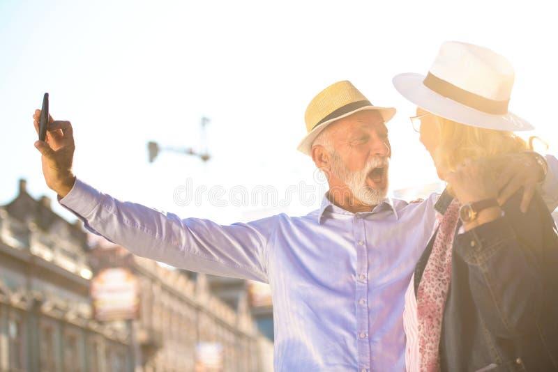 Tourisme et technologie Couples supérieurs de déplacement prenant le selfie ensemble sur le fond guidé photo stock