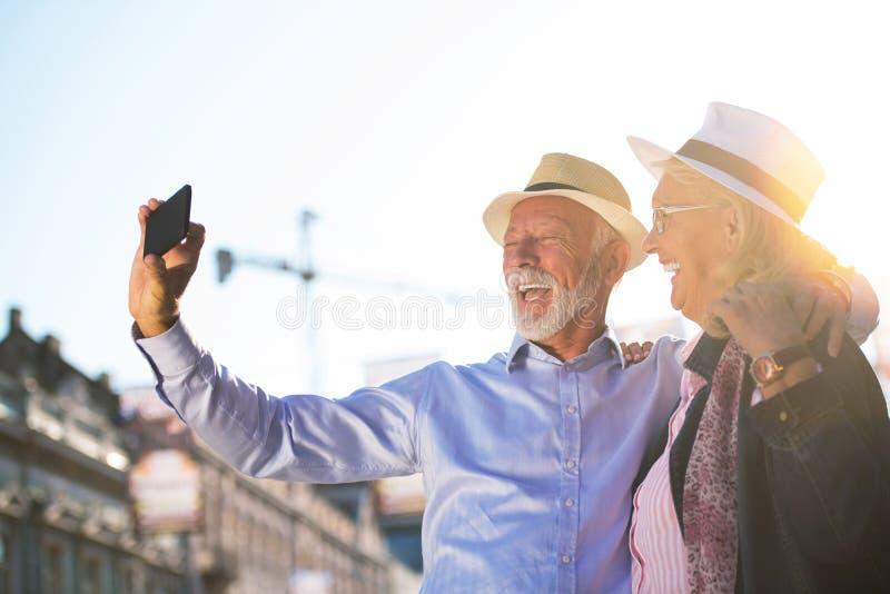 Tourisme et technologie Couples supérieurs de déplacement prenant le selfie ensemble sur le fond guidé images libres de droits