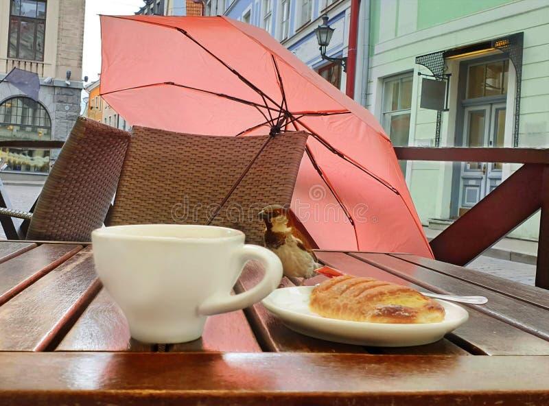 Tourismus in der Europa-Straßencafétabelle mit Tasse Kaffee-Regenschirm auf Stuhl und Spatz sitzen auf süßer Kuchenreise Tabellen lizenzfreies stockfoto