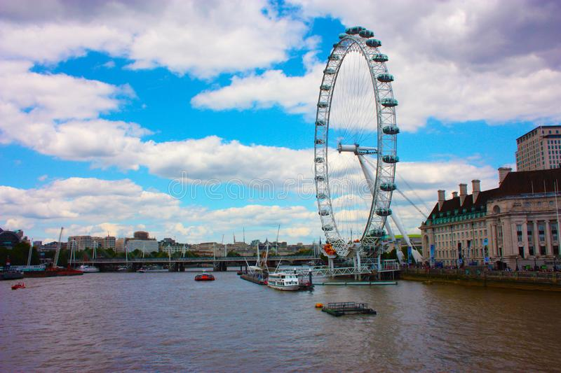 Tourist afternoon in Westminster City. The Ferris wheel or Eye of London rules over the water of the River Thames. In UK royalty free stock image