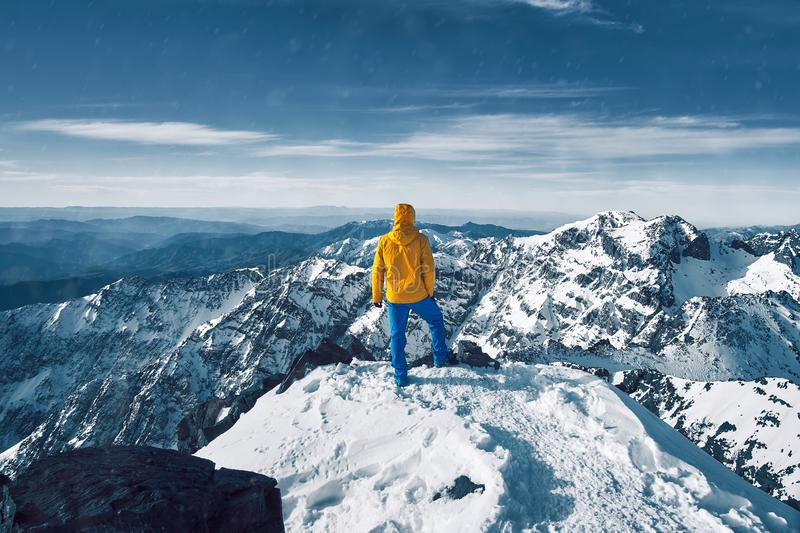 Tourist alone standing and meditating over snow covered Atlas mountain range royalty free stock photos