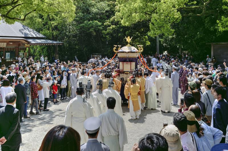 Tourist around men carrying an altar in Atsuta Shrine, Nagoya, Japan. Crowd tourist group around group of men carries an altar with phoenix during the stock images