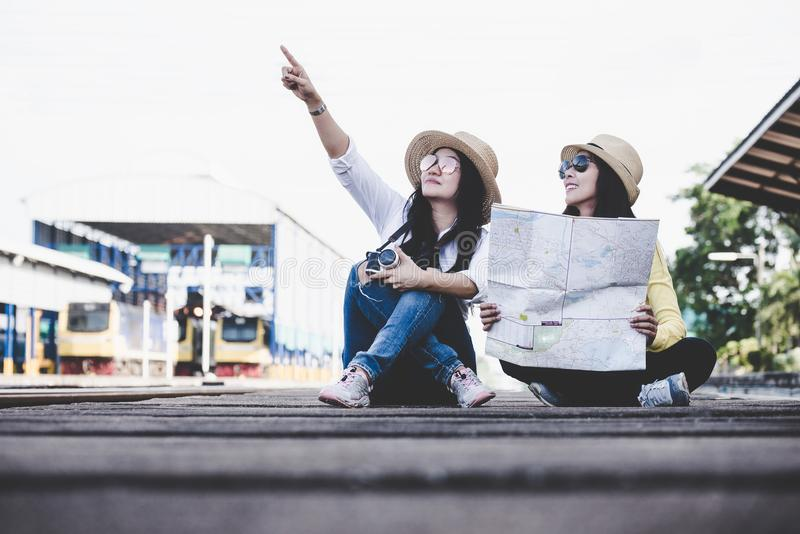 Tourist asian lifestyle friends women wearing backpack holding map, traveler siting for waiting a train, royalty free stock photo