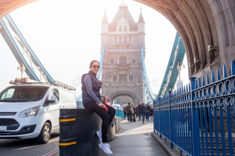 Tourist asian woman relaxing by the Tower Bridge London in summer day. royalty free stock image