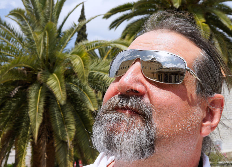 Tourist on a background of palm trees in glasses stock photos