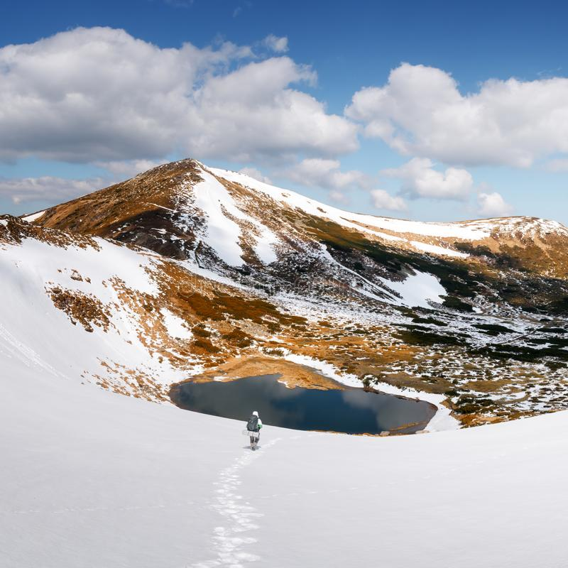 Tourist with a backpack. Amazing landscape with lake in spring snowy mountains royalty free stock photos