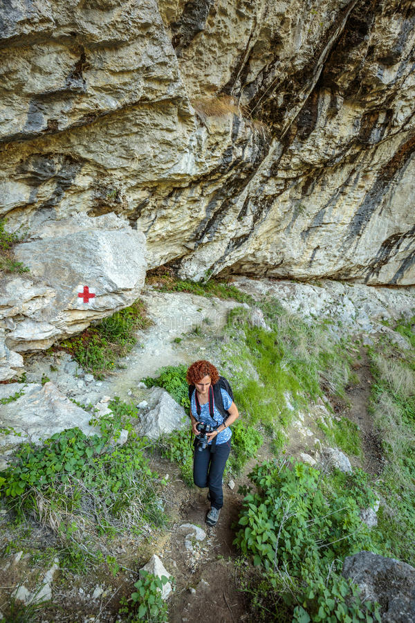 Tourist with backpack and camera. Hiker woman with camera and backpack on a trail in mountains royalty free stock photography