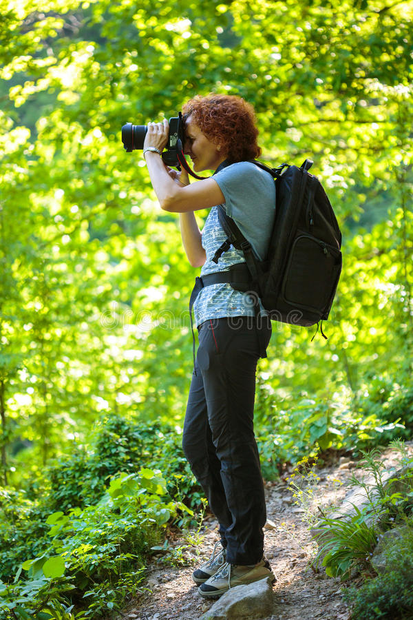 Tourist with backpack and camera. Hiker woman with camera and backpack on a trail in mountains stock image