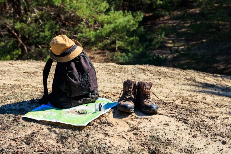 Tourist backpack with hiking boots, hat, compass and map on the glade in pine forest. Trekking hike gear equipment. Travel concept royalty free stock photo