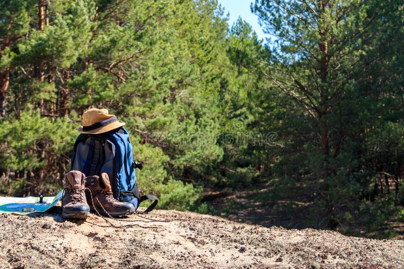 Tourist backpack with hiking boots, hat, compass and map on the glade in pine forest. Trekking hike gear equipment. Travel concept royalty free stock images