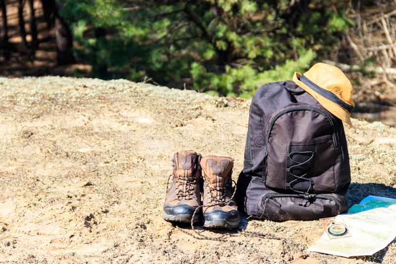 Tourist backpack with hiking boots, hat, compass and map on the glade in pine forest. Trekking hike gear equipment. Travel concept royalty free stock photos