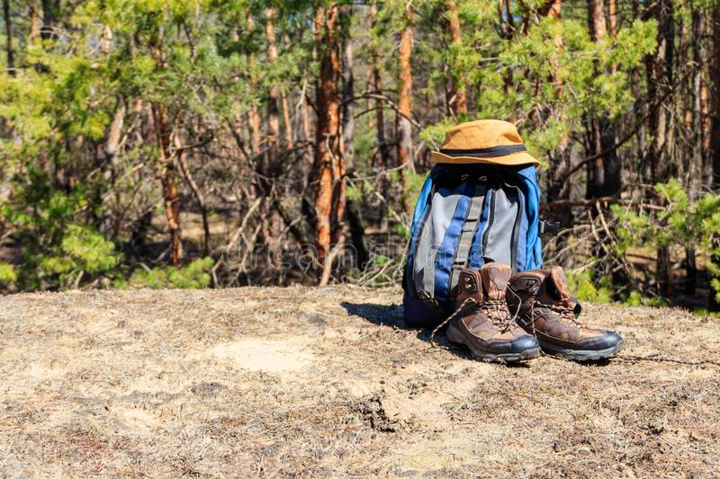 Tourist backpack, hiking boots and hat on the glade in pine forest. Tourist backpack, hiking boots and hat on the glade in the pine forest. Hike concept stock photo