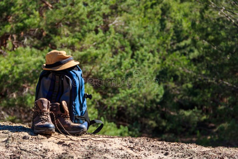 Tourist backpack, hiking boots and hat on the glade in pine forest. Hike concept stock image