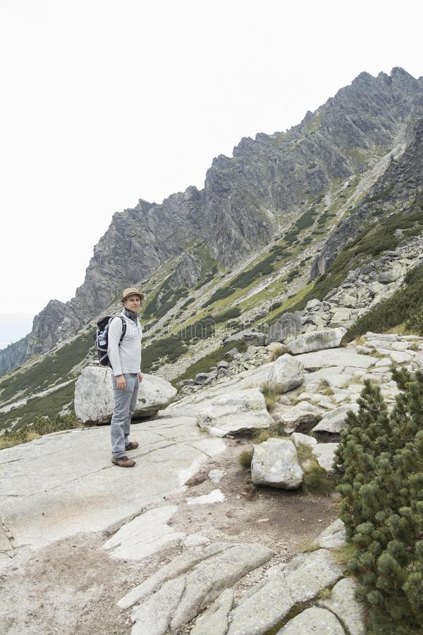 Tourist with backpack hiking in moutains stock images