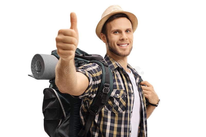 Tourist with a backpack making a thumb up sign. Isolated on white background stock photography