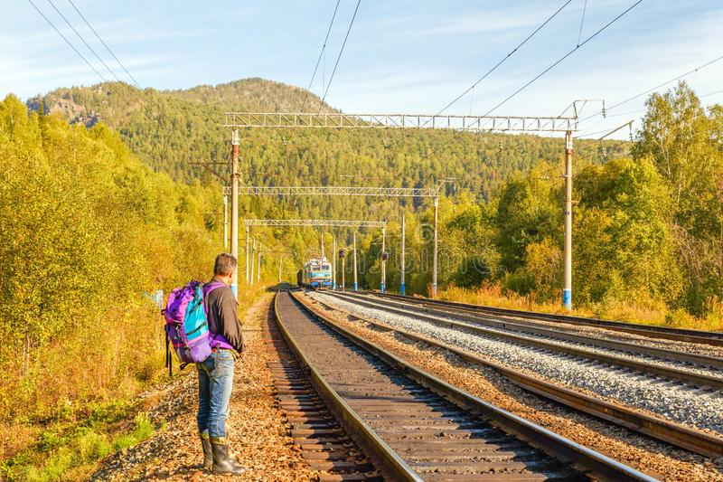 A tourist with a backpack is near the Ufa-Beloretsk railway in the Ural Mountains. Russia, Bashkortostan, September 2016. A tourist with a backpack is near the stock photo
