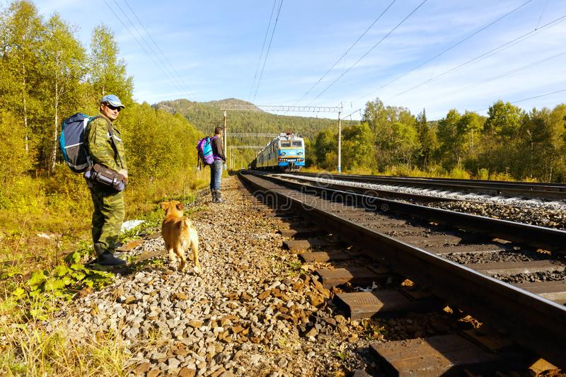 A tourist with a backpack stands near the railway in the Ural Mountains. The train is moving by train. Russia, Bashkortostan, September 2016: A tourist with a stock photo