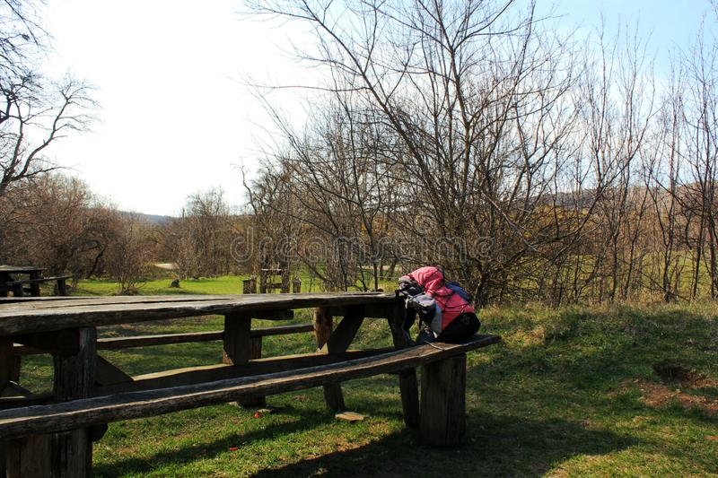 Tourist backpack on a wooden bench in the park. Tourist backpack lies on a wooden bench in the park, a wooden table and a bench in the forest, for holidaymakers royalty free stock photography